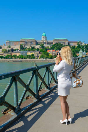 sights: Blonde tourist on her trip to Budapest making pictures of Buda Castle from the famous Chain Bridge