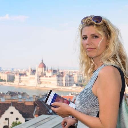 Aantrekkelijke blonde vrouwelijke reiziger met een reisboek in het centrum van Boedapest. Patroon op de cover is gegenereerd voor dit beeld.