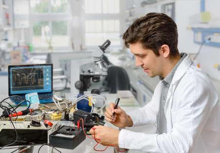 ingenieria elÉctrica: Tecnología o ingeniero reparaciones masculinos energéticos joven equipo electrónico en el centro de investigación. Shallow DOF, se centran en la cara del trabajador.