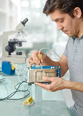 vaccuum: Young male tech cleans faulty computer processor in hardware repair workshop