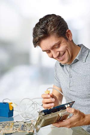 componentes: Sonreír tecnología masculina limpia procesador de la computadora defectuosa en el taller de reparación de hardware