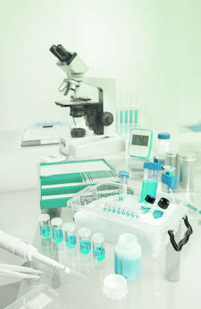 analytical chemistry: Scientific background with samples, pipette, ice basket and microscope in gray and blue, space for your text on the top
