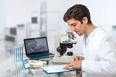 cancer research: Male scientist or tech with dark hair and brown eyes works in research facility