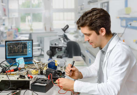 oscilloscope: Young energetic male tech or engineer repairs electronic equipment in research facility. Shallow DOF, focus on the face of the worker. Stock Photo