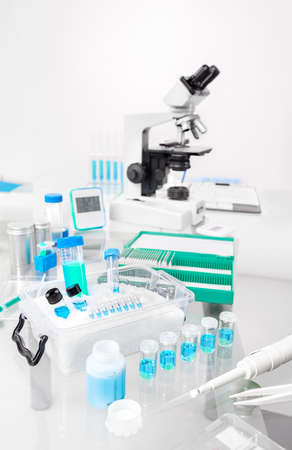 slide glass: Scientific background with samples, pipette, ice basket and microscope in gray and blue, space for your text on the top