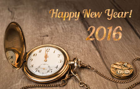 five to twelve: Vintage watch on a wooden background showing five to twelve and caption Happy Year 2016 Stock Photo