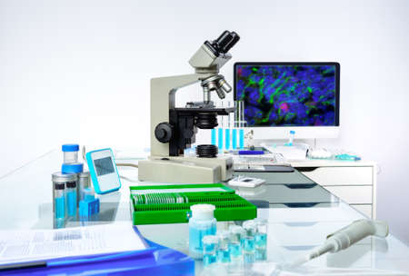histological: Microscopic work station. Microscope, computer monitor with digital fluorescent image and tools for histological staining of tissue to detect cancer and analyze morphological abnormalities in patients tissue. Stock Photo