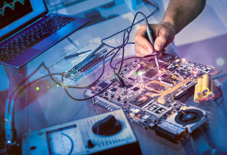 circuitos electricos: Correcciones Tech placa en su centro de servicio. Shallow DOF, se centran en la mano, la imagen está entonado con efectos de luz adicionales Foto de archivo