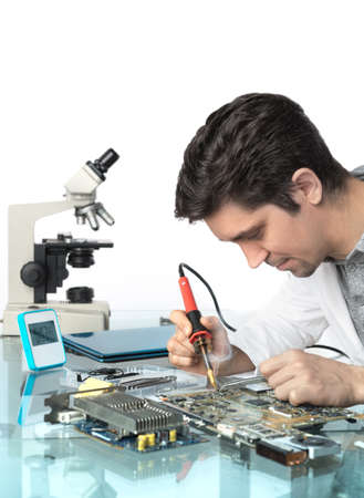 electronics: Young energetic male tech or engineer repairs electronic equipment, top of the picture isolated, space for your text, focus on the solrer tip and eyes Stock Photo