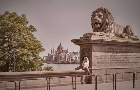 building a chain: Blond female tourist sits on the parapet of famous Chain Bridge in Budapest with a view on Parliament building across the river