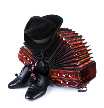milonga: Bandoneon, pair of tango shoes, necktie and a black hat on white background Stock Photo