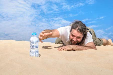 Dorstige man in de woestijn bereikt voor een fles van zuiver water