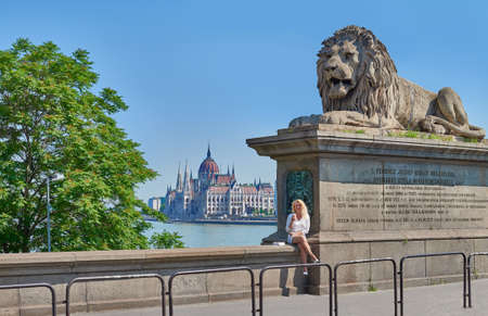 budapest: Blond female tourist sits on the parapet of famous Chain Bridge in Budapest with a view on Parliament building across the river