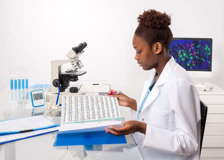 African-american biologist checks records in scientific lab or research facility
