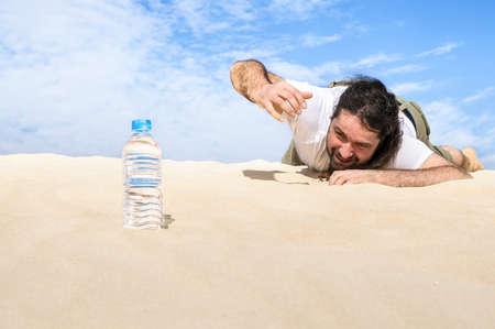 sediento: Hombre sediento en el desierto llega por una botella de agua pura