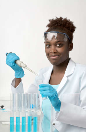 laboratorio: Cient�fico o graduado estudiante afro-americana en bata de laboratorio y gafas de protecci�n trabaja con muestra l�quida