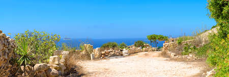 green plants: Typical Maltese stone shed facing the sea on a bright sunny day. Malta, stone cliffs close to Zurrieq. Stock Photo