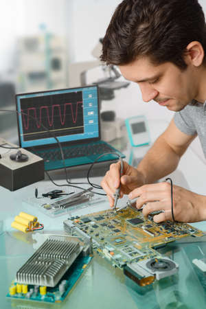 Jonge energieke man tech of ingenieur reparaties elektronische apparatuur in onderzoek faciliteit. Ondiepe DOF, focus op het gezicht van de werknemer. Stockfoto