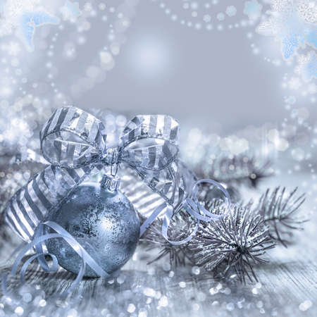 greeting christmas: Christmas greeting card with toys and decorations in silver and blue, space for your text. Shallow DOF, focus on the stripy bow. Stock Photo