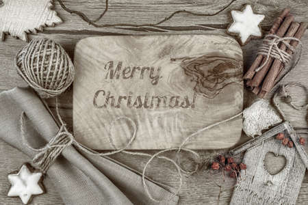 decorated: Greeting card Merry Christmas burnt on wooden board with winter decorations around. This image is toned