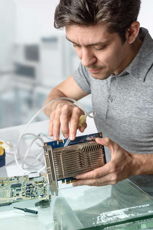 vaccuum: Young male tech cleans faulty computer processor in hardware repair workshop. Focus on the face and fingers