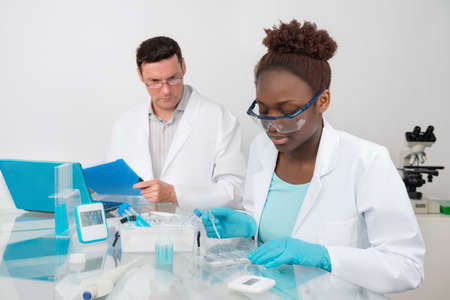 medical laboratory: Scientists, male and female, work in research facility. Mature scientist supervises work of younger colleague. Focus on the eyelashes of female  student