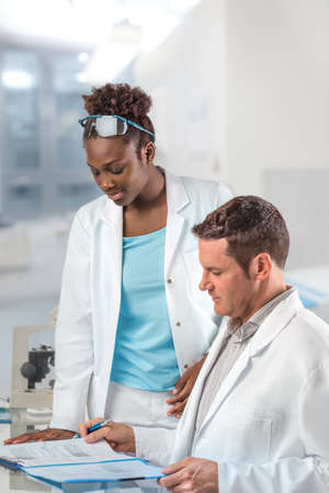 lab coats: Scientists, male and female, work in research facility