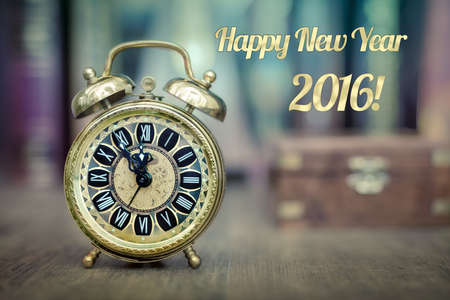 five to twelve: Vintage alarm clock showing five to twelve in the study room. Happy New Year 2016! Stock Photo