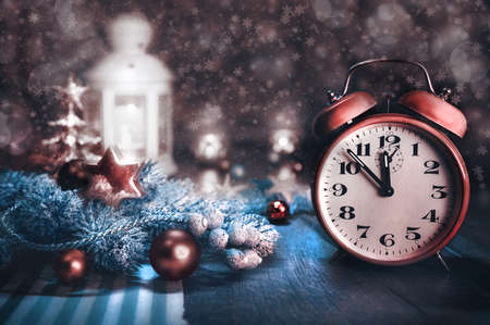 five to twelve: Happy New Year! Greeting card with alarm clock showing five to twelve and winter arrangement. This image is toned. Focus on the clock.