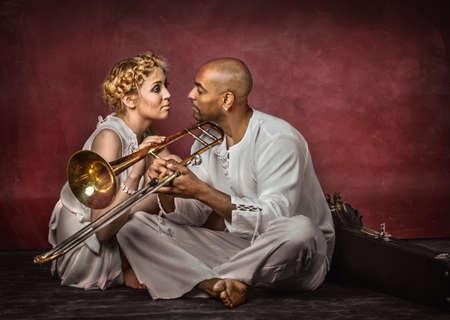 trombon: Mujer europea hermosa y atractiva trombonista cubano sobre fondo rojo oscuro, tiro del estudio Foto de archivo
