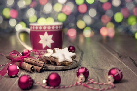 Hot drink, Christmas cookies and cinnamon sticks on decorated table, toned image