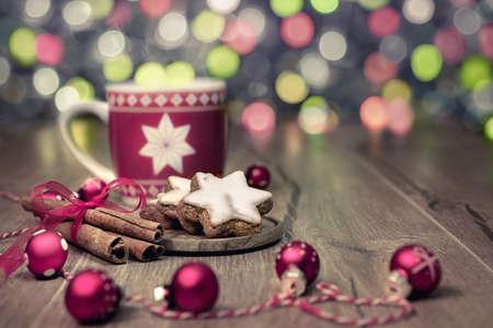 tea trees: Hot drink, Christmas cookies and cinnamon sticks on decorated table, toned image