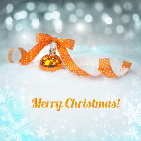 Orange Christmas bauble on a neutral winter background with a caption