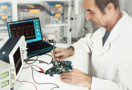 hardware repair: Senior male tech works in hardware repair facility. This image is toned Stock Photo