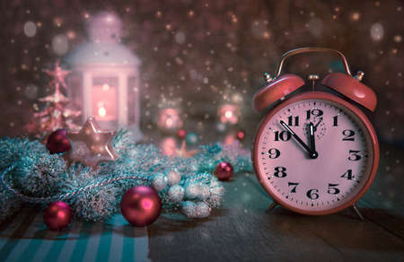 five to twelve: Happy New Year! Greeting card or banner design with alarm clock showing five to twelve and winter arrangement. This image is toned. Focus on the clock.