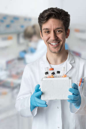 scientist man: Smiling male scientist with brown eyes and curly hair holds box of samples Stock Photo