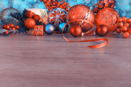 blue border: Christmas border with orange and blue baubles and berries on wood. Shallow DOF, focus on the red bal with Star pattern. Space for your text. This picture is toned Stock Photo