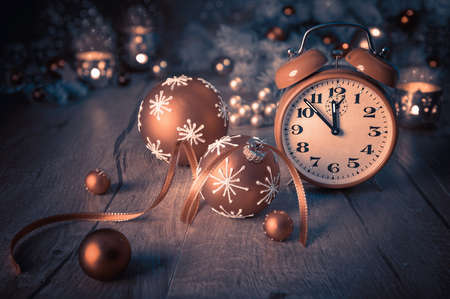 five to twelve: Happy New Year! Vintage alarm clock showing five to twelve on wood. This image is toned. Focus on the clock. Stock Photo