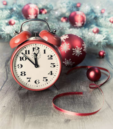 five to twelve: Happy New Year! Greeting card with alarm clock showing five to twelve and winter decorations on wood. This image is toned. Focus on the clock. Stock Photo