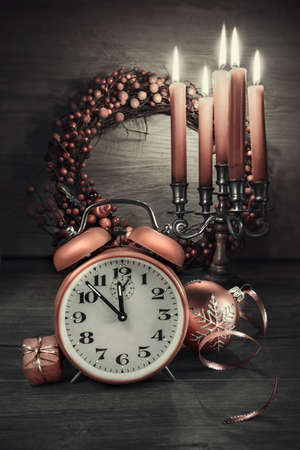 this: Happy New Year! Vintage alarm clock showing five to twelve on wood. This image is toned. Focus on the clock. Stock Photo