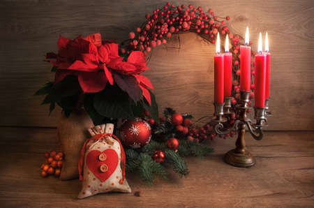 Christmas greeting card with candles and decorated Christmas tree on wooden table. This image is toned.