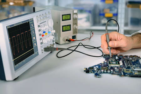 Tech fixes motherboard in service center. Shallow DOF, focus on hand, part of moherboard and front part of oscilloscope. This image is toned. Banque d'images