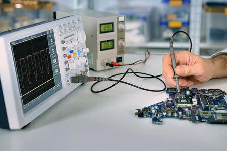 Tech fixes moederbord in service center. Ondiepe DOF, focus op de hand, een deel van moherboard en het voorste deel van de oscilloscoop. Deze afbeelding is afgezwakt. Stockfoto