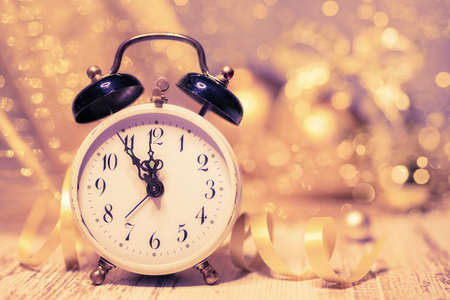 abstract alarm clock: Greeting card design Happy New Year! with vintage alarm clock showing five to midnight on abstract glitter background. Space for your text. Shallow DOF, focus on the clock hands and numbers. This image is toned.