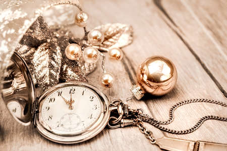 number 12: Vintage pocket clock showing five to twelve. Happy New Year! This image is toned. Shallow DOF, focus on the number 12 and ends of the clock hands