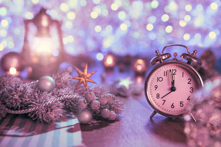 twelve month old: Old alarm clock showing five to midnight and glittering decorations. Happy New Year 2016! This image is toned.
