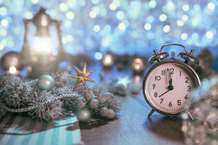 12 month old: Old alarm clock showing five to midnight and glittering decorations. Happy New Year 2016! This image is toned.