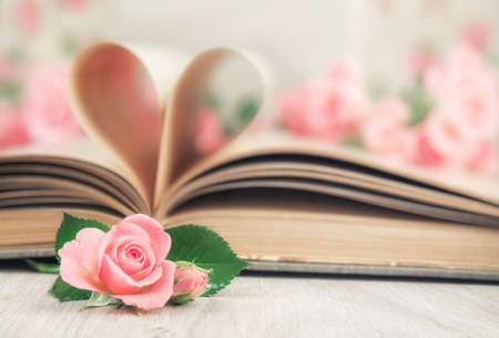 book pages: Pages of an old book curved into a heart shape and little pink roses on wooden table. Valentines day card.