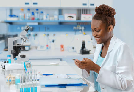 Afrikaans-Amerikaanse bioloog in het lab sms'en iemand op haar mobiel met een glimlach