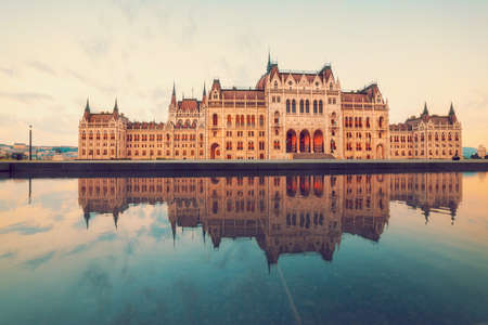 reflection: Parliament building in Budapest on a sunrise with reflection in fountain. This image is toned